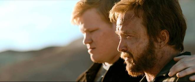 Todd puts his arm around Jesse as they sit together in the desert after burying Todd's housekeeper