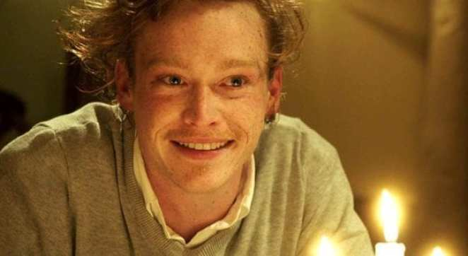 Jeremy (Caleb Landry Jones) sits with lit candles in front of him.