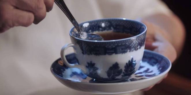 A blue and white delft tea cup and silver spoon