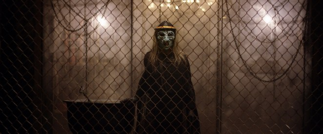 a figure in a witch mask stands behind a wire fence