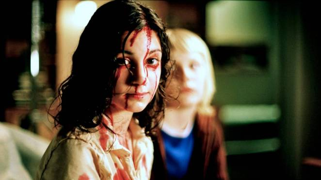 A young girl with blood streaming down her face looks calmly into the camera while a blond boy sits behind her out of focus from Let the Right One In