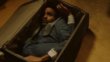A man is contorted inside a suitcase, looking up frightened.