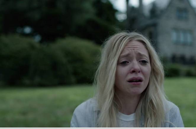 Angela cries with a large house and its hedges in the background