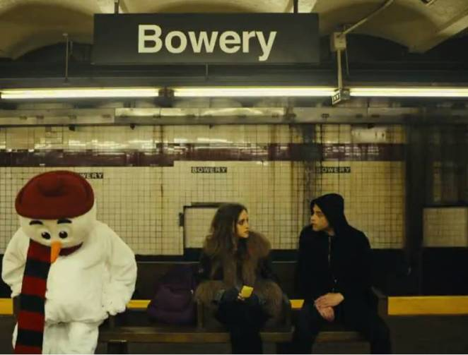 Elliot and Darlene sit on a subway bench at the Bowery stop in Manhattan with a snowman