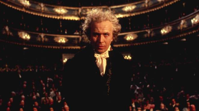 An elderly Beethoven stands on a stage, his back to the audience