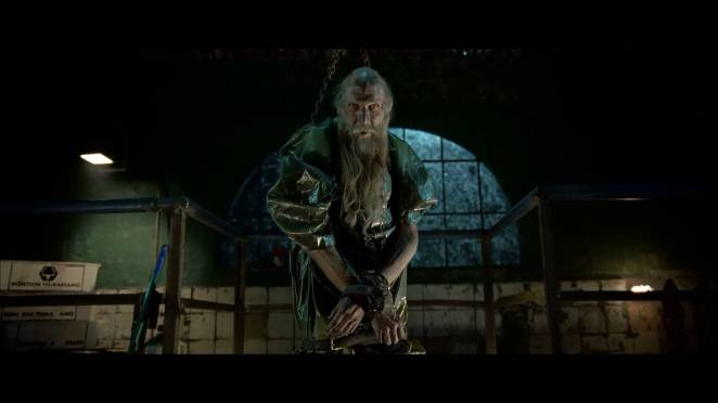 A dirty, skinny old man with a long beard is chained up in a warehouse in Rare Exports: A christmas tale