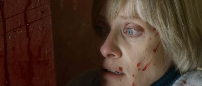 Barbara Crampton has blood on her face as she stares out of a window in We Are Still Here