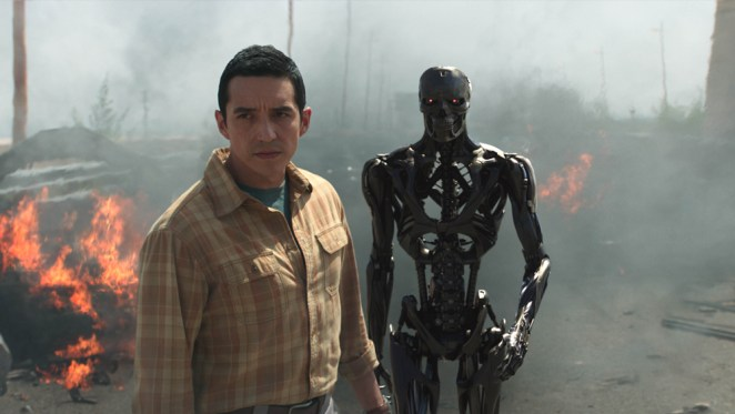 Rev-9 and his robot counterpart look to the distance surrounded by fire