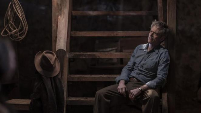 Major Bowen sits on some wooden steps, watching Amy