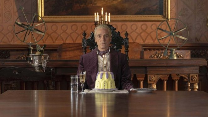 Veidt on his anniversary sitting at a dining table with a large cake in front of him