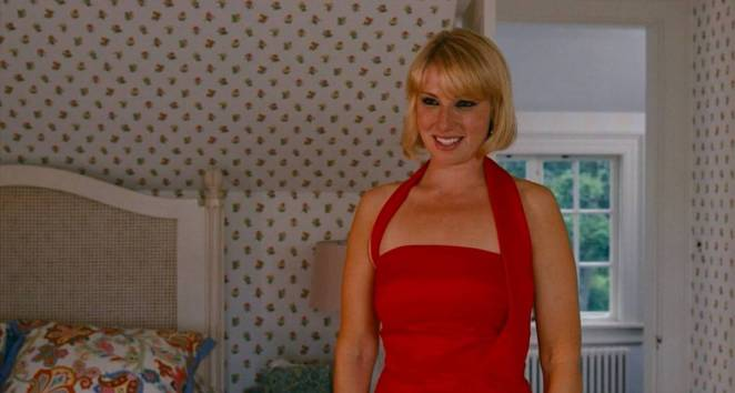 Ari Graynor as Daisy Darling, standing in her bedroom wearing a red dress for her engagement party