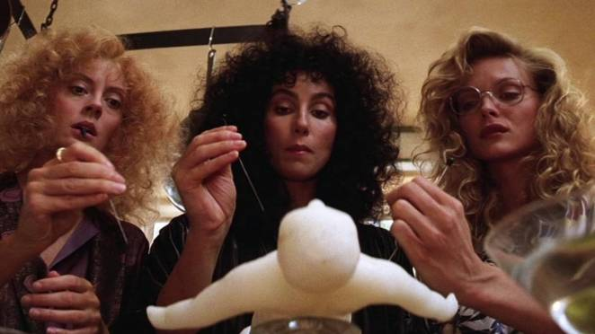 The three witches played by Susan Sarandon, Cher and Michelle Pfeifer gather around a wax voodoo doll