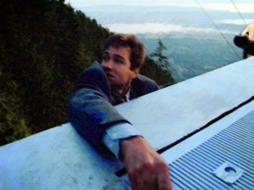 Mulder hangs on from the top of the cable car as he's taken up to the top of a mountain.