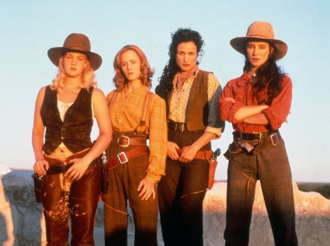 The women of Bad Girls pose in stereotypical Cowboy fashion, with either their hands to their guns or their arms crossed..