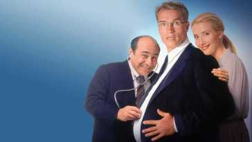 Larry holds a stethoscope to a pregant Alex's stomach, with Diane behind him.