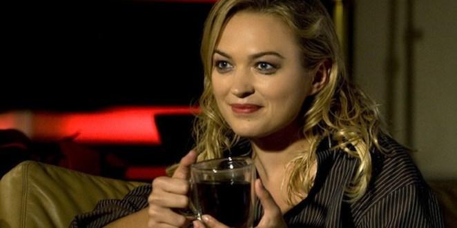 Beth holding a drink, wearing striped shirt, staring ahead, sitting on a couch