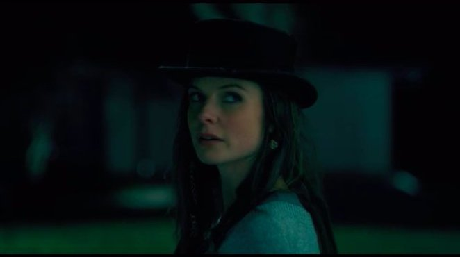 A woman in a hat looks at someone from afar