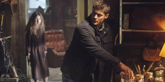 Dean standing, one hand gripping the lid of a jar and looking behind him, creepy little girl lingers in the background watching him
