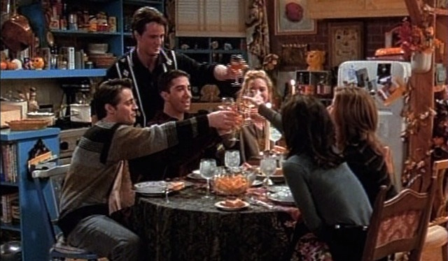 The friends cast sit around a table, toasting wine glasses together after all their Thanksgiving plans had fallen apart.