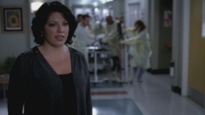 Callie Torres looks down a hospital corridor, while a bunch of people in scrubs rush in medical equipment behind her