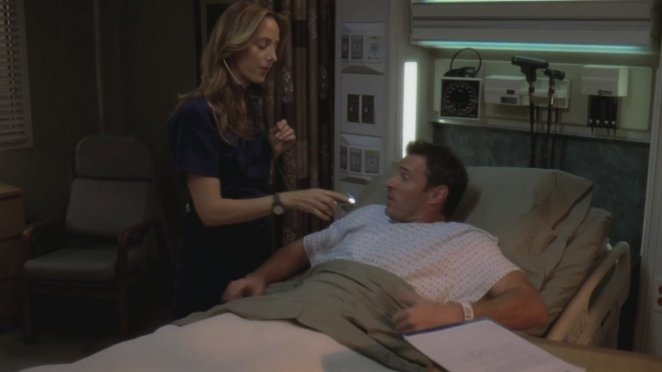 Teddy checks Henry's heart while he rests in a hospital bed. She tries not to laught.
