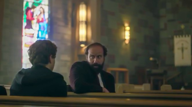 Finklestein and Peter sit in an old church with large stained glass windows
