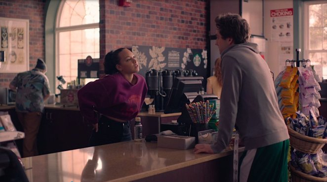 Chloe stands behind the counter at the coffee shop flirting with Brendan, who stands on the other side