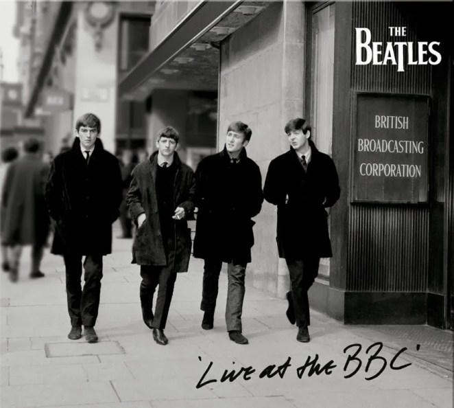 In Black and white, the four beatles, still in their clean cut early days, walk down the street together, on their way to the BBC studios.