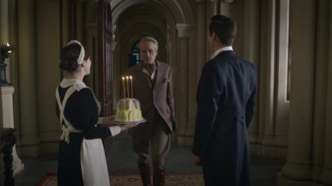 Watchmen - Veidt walks towards Mr Philips and Ms Crookshanks holding an anniversary cake with 3 candles