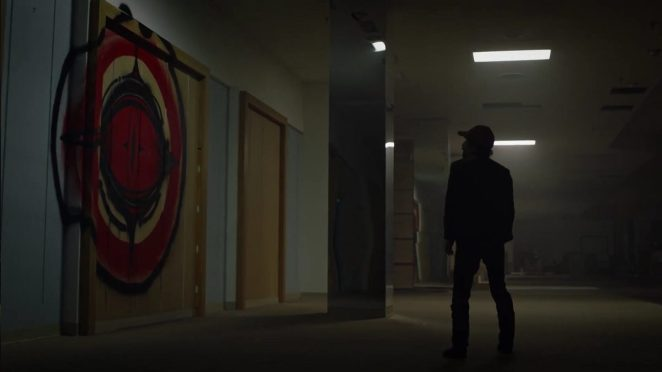 Watchmen - Wade stands in an abandoned department store, looking at a spray painted large red eye logo on the wall