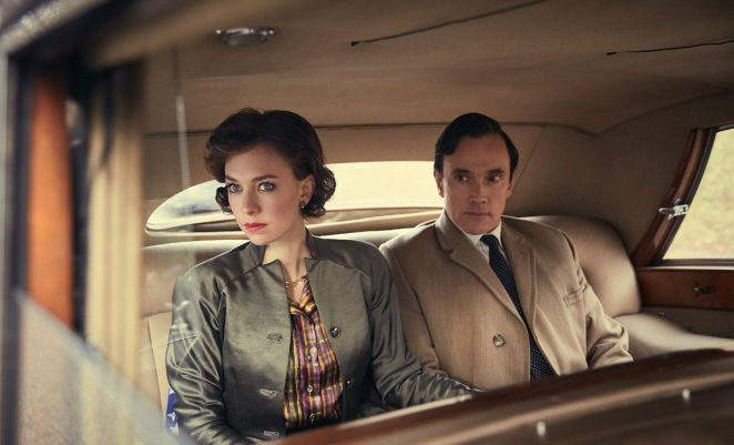 Margaret and Peter ride in the back of a car, watching the crowds while dressed in smart clothes