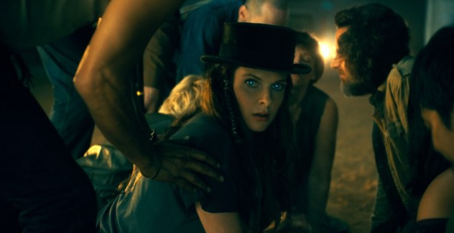 A woman in a hat stares away from a group of people hovering over a body