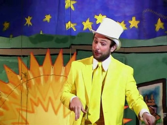 Charlie in a yellow suit with top hat and cane performing his surprise number at the end of The Nightman Cometh