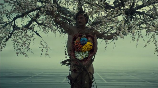 A murder victim, upright, with a tree growing out of him, and the insides of his chest and stomach cavity replaced by different flowers