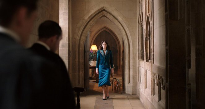 Mrs Coulter, in a smart blue suit, enters the entrance hall of Jordan College