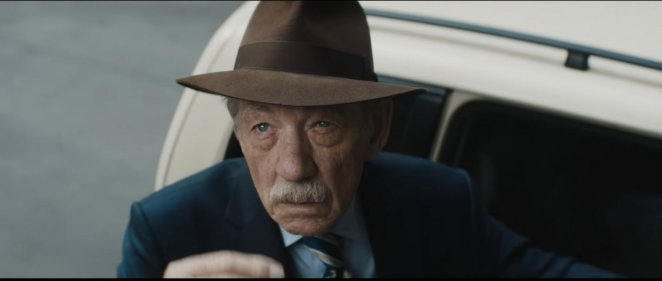 A man in a hat and suit gets out of a car