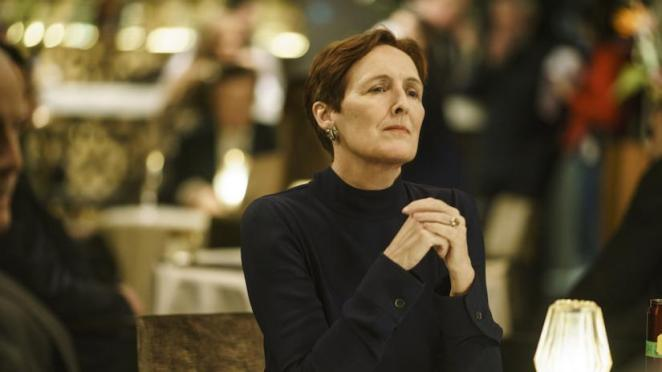 Fiona Shaw as her character in Killing Eve sitting at a table and clutching her hands