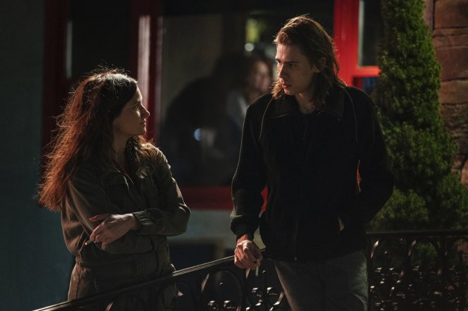 Eve and Julian stand outside the bar smoking cigarettes and talking