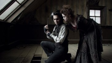 Sweeney kneels, holding a razor. Mrs Lovett leans in behind him, and he looks over his shoulder back at her