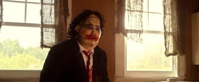Leatherface sits in a chair in his suit and female mask on