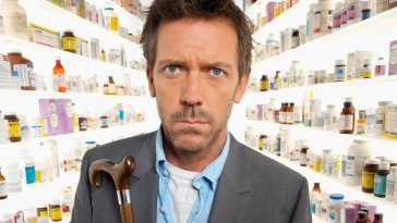 House, looking bemused, stands facing the camera with a corridor of floor to ceiling prescription medication behind him