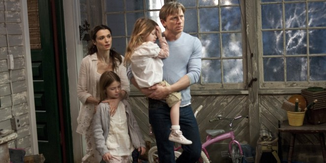 Rachel Weisz and Daniel Craig in Dream House, staring at something in fear ahead of them, while Craig holds one little girl and Weisz holds the other little girl close to her, a hand over the girl's chest inside a room