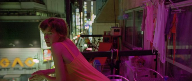 Scene early on in Enter The Void. Girl leaning over balcony with a blur of bright colours in the background
