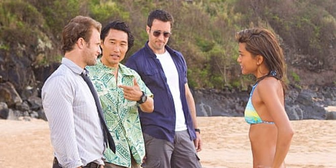 Steve looking at Kono in sunglasses, Chin pointing to Danny, Danny pointing straight ahead, Kono standing in front of the three men with her hands on her hips on the beach in Hawaii Five-0