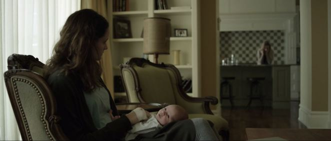 Mary sits on the couch and holds the baby as she stares at Rachel in the kitchen in Still/Born