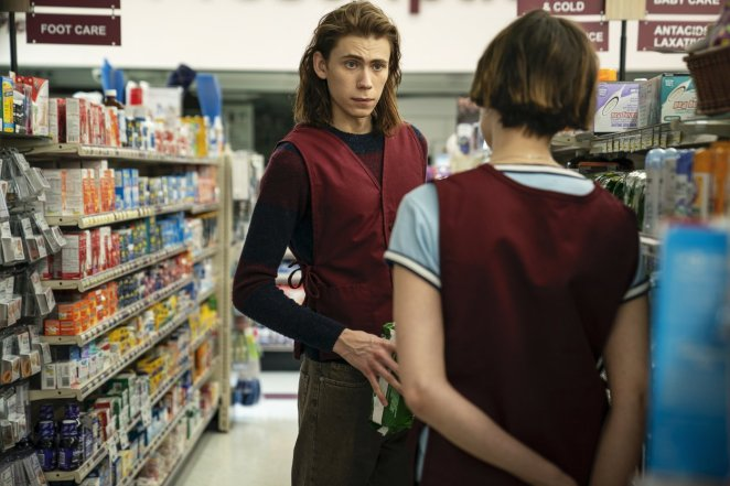 Julian stands in the aisle of the pharmacy talking to his female coworker