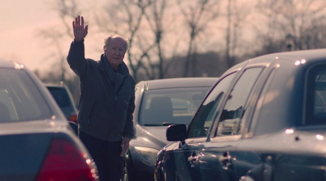 Roy Rafferty stands in a parking lot and waves to Eve