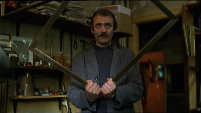 Bruno Ganz as Zimmermann holding a picture frame