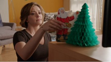 Rebecca puts a santa ornament next to a Christmas tree ornament