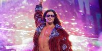 John morrison stood in front of his pyro wit his arm raised